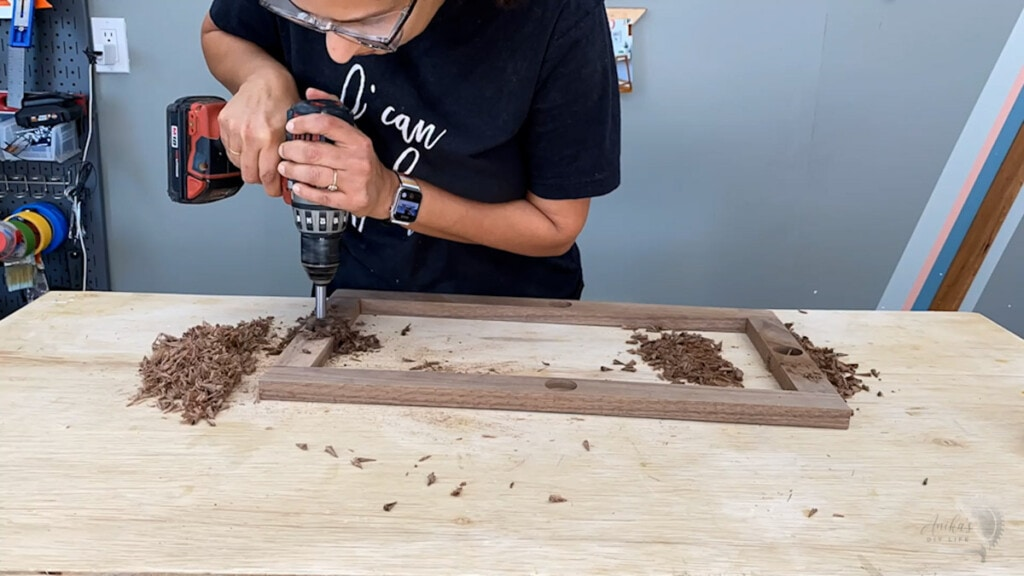 woamn drilling holes into the walnut frame using a Forstener bit