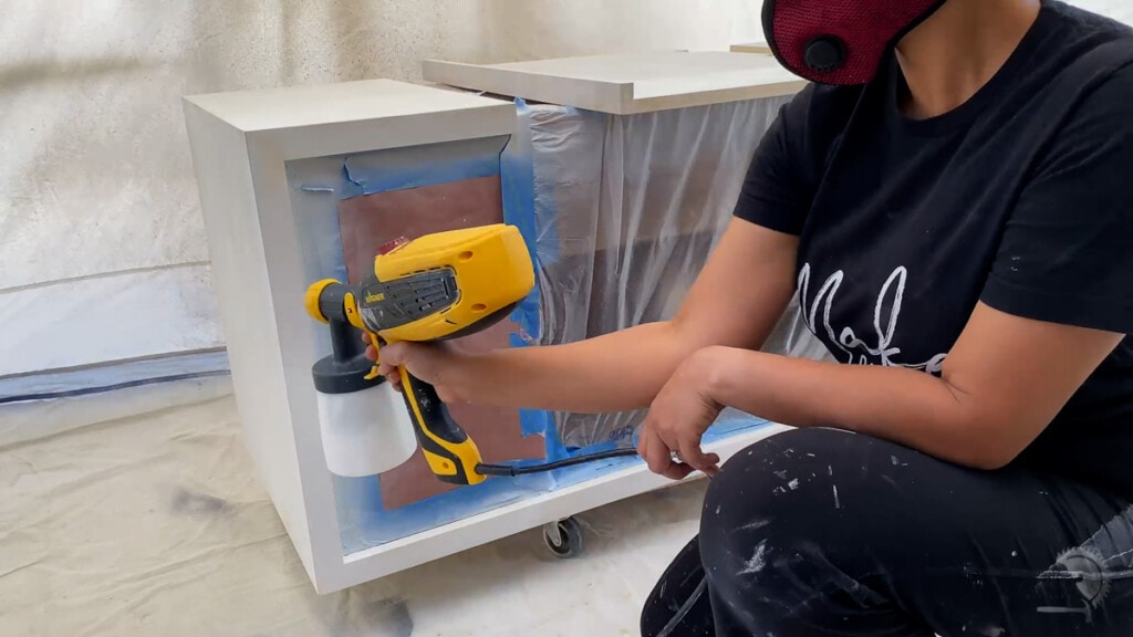 painting the exterior of the console table white with a paint sprayer
