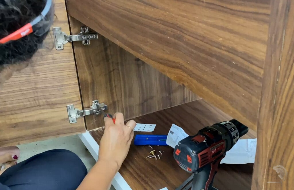 Woman attaching a door to the cabinet