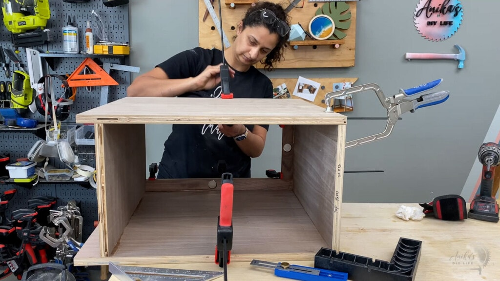 woman building the speaker compartments for the diy record player stand