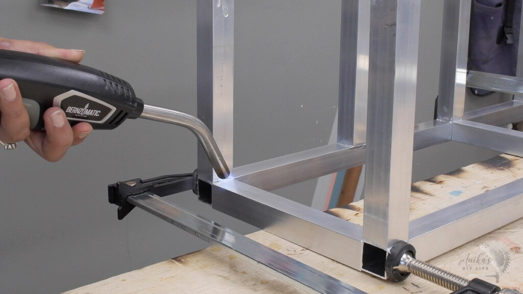 Woman brazing aluminum tubes to build a metal plant stand