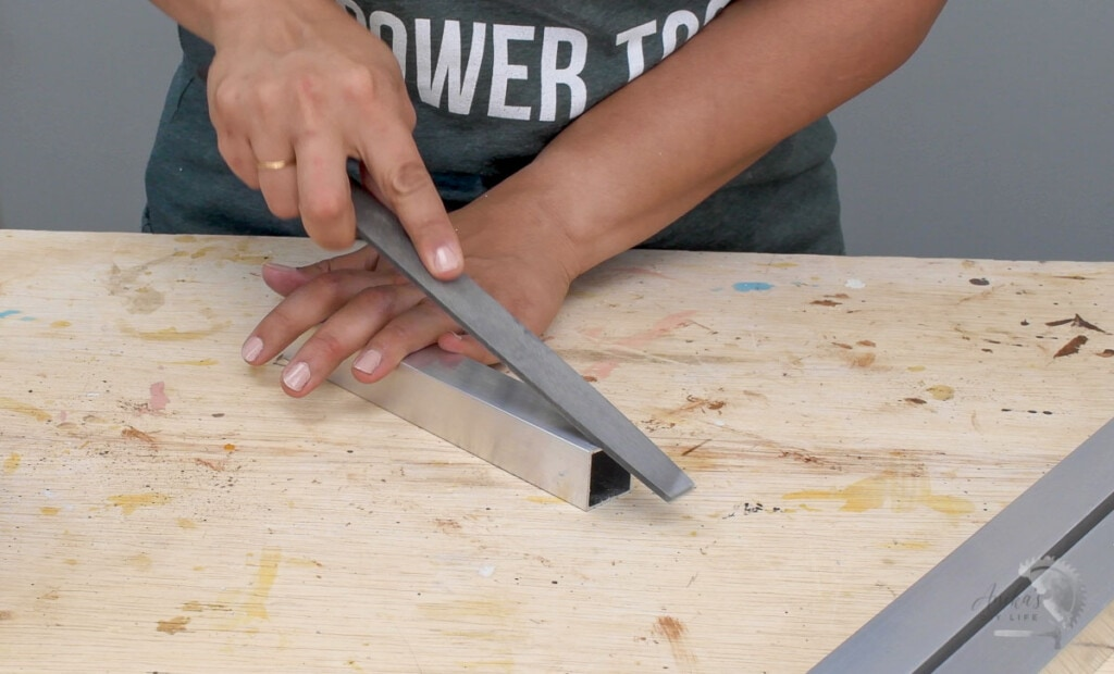 Woman filing the edge of an aluminum tube with a metal file.
