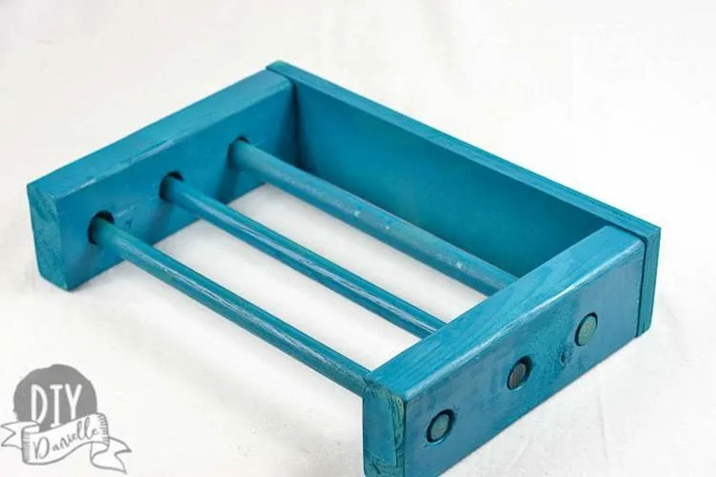 Turquoise painted organizer for kitchen wrap made from scrap 2x4s and dowels