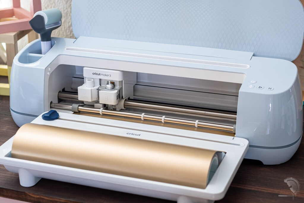 Cricut Maker 3 with roll holder loaded with gold vinyl.
