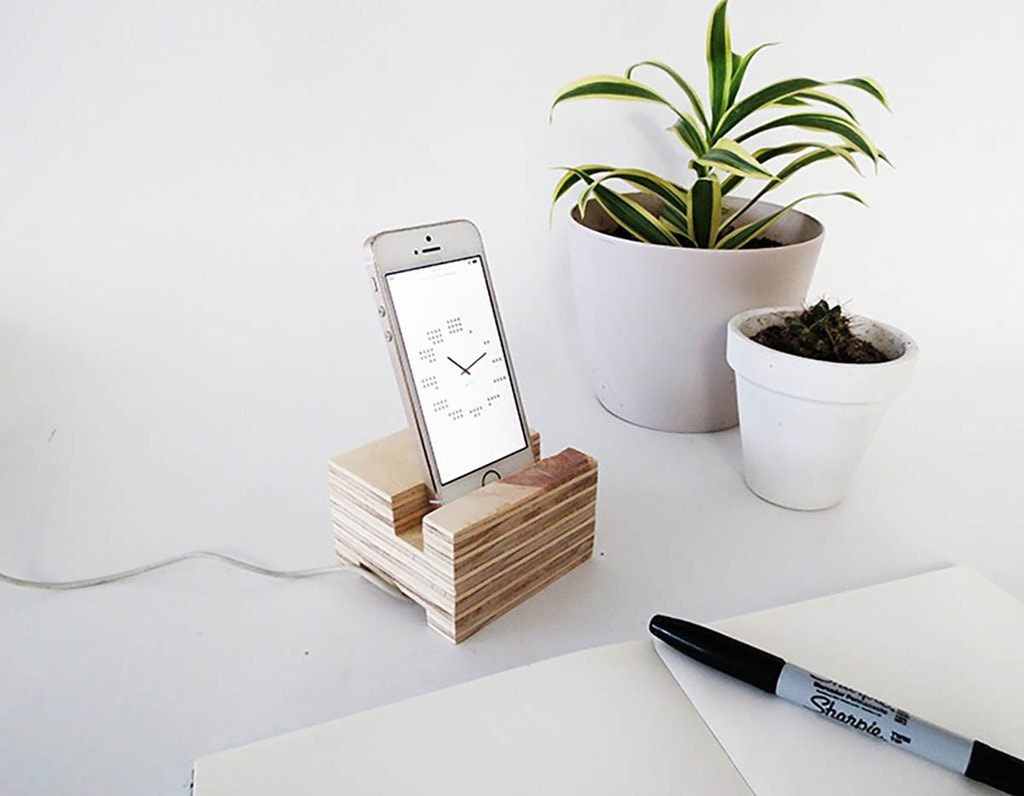 scrap plywood phone holder with iPhone sitting next to pen and notebook