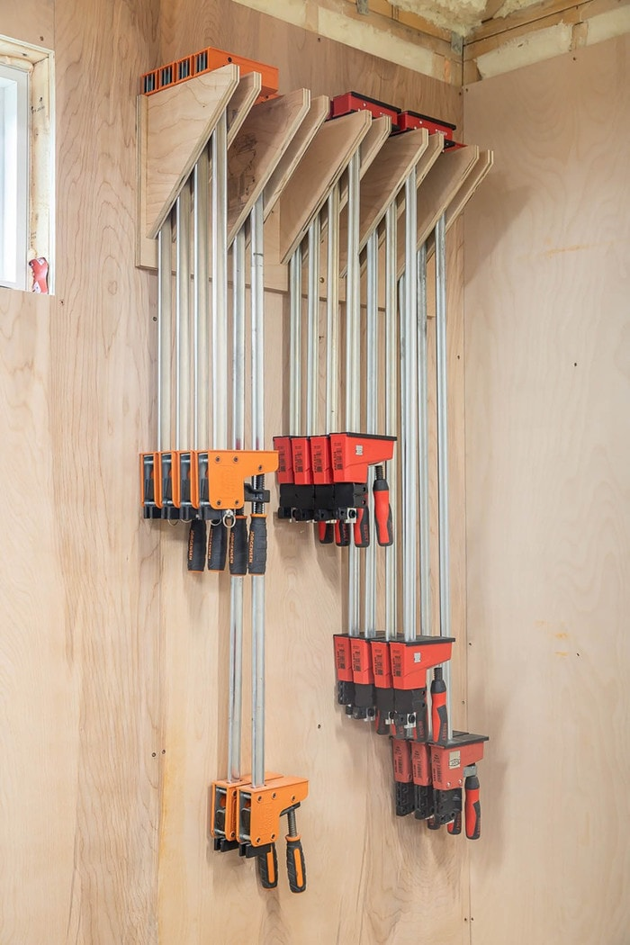 wood clamps hanging on the wall in an organizer