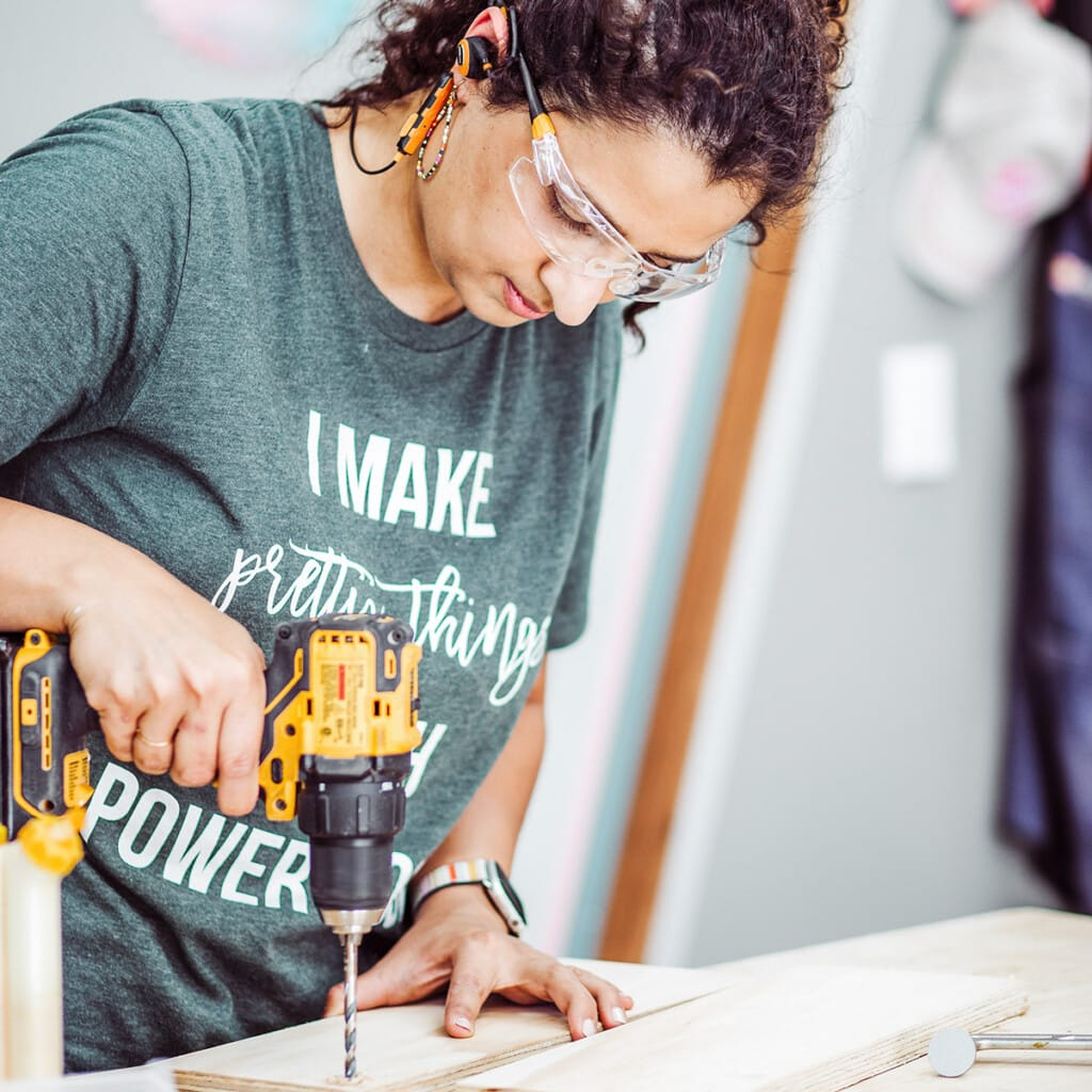 woman working with drill on workbench