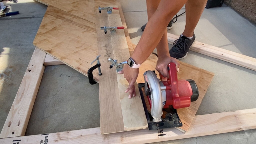 Woman using a plywood jig to make a straight cut with a circular saw