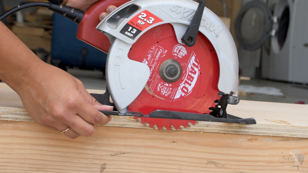 woman setting the depth of blade on the circular saw