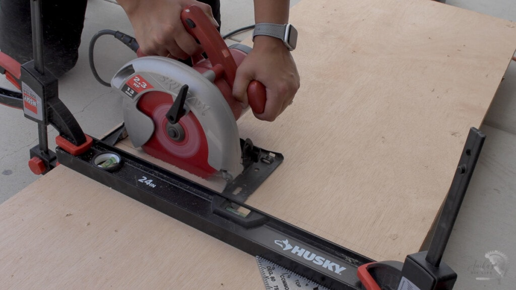 woman making the cut on a sheet of plywood using a circular saw