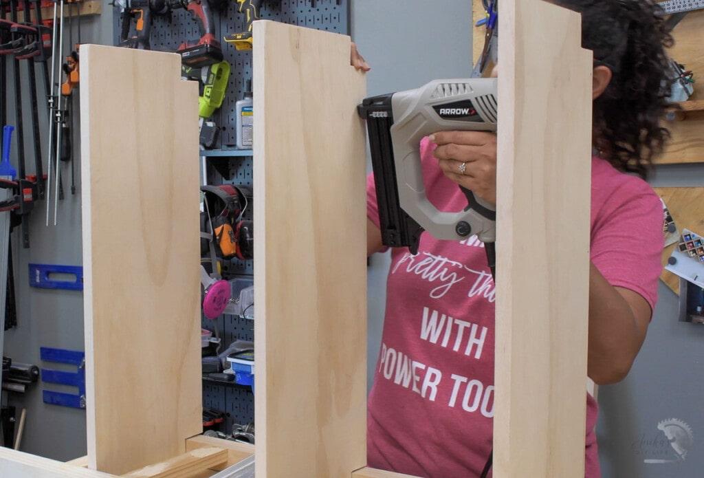 Woman attaching shelves to the DIY bookshelf