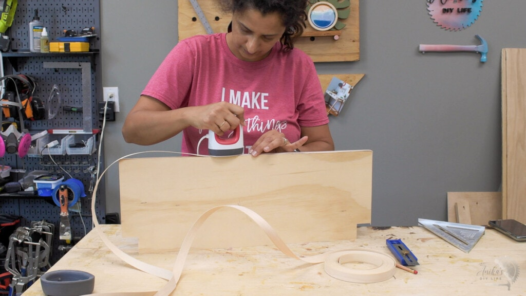 woman applying edge banding to a sheet of plywood