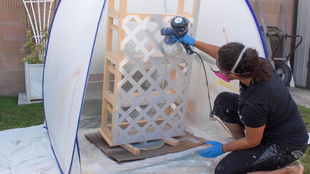 Woman spraying paint on a DIY trellis bookshelf