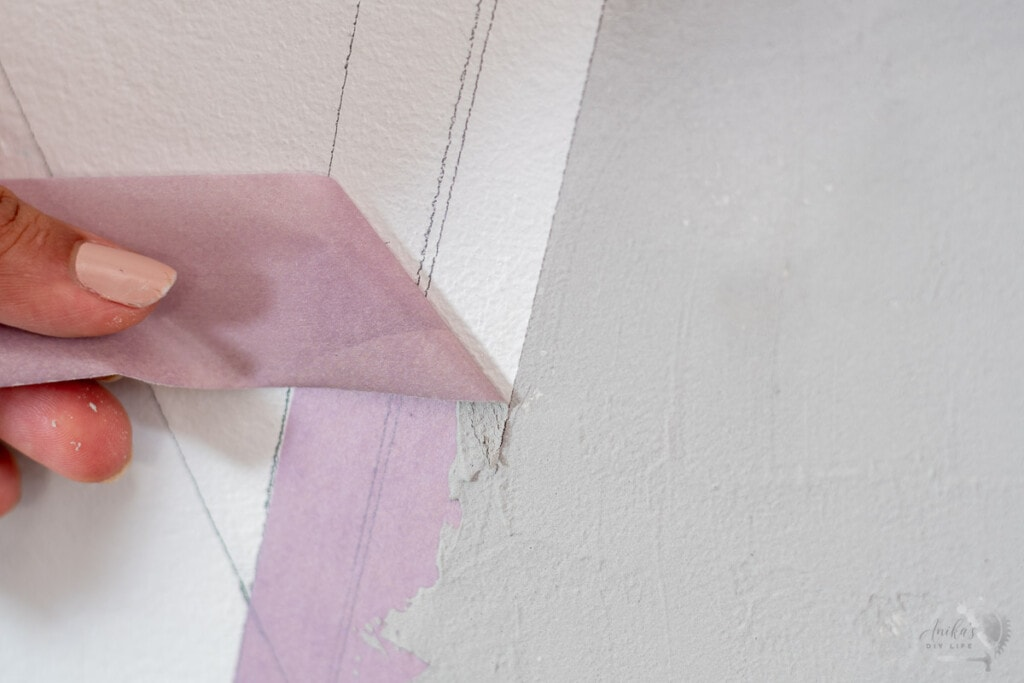 Woman pulling off tape from the DIY concrete wall