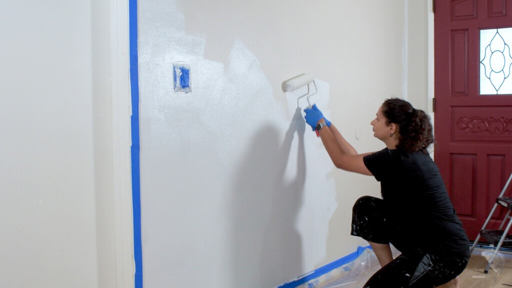 Woman painting a wall white with a paint roller