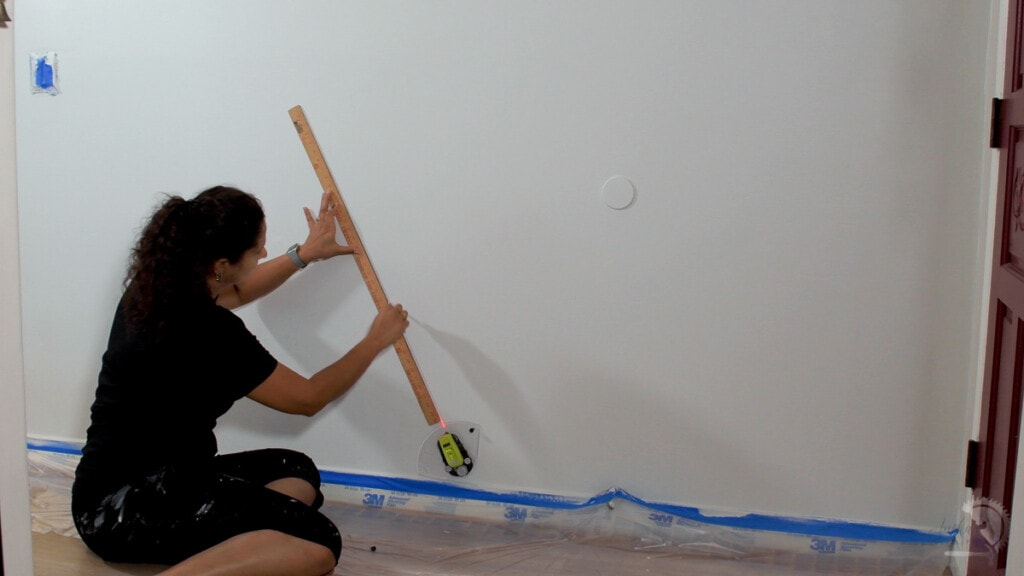 Woman drawing lines on a white wall