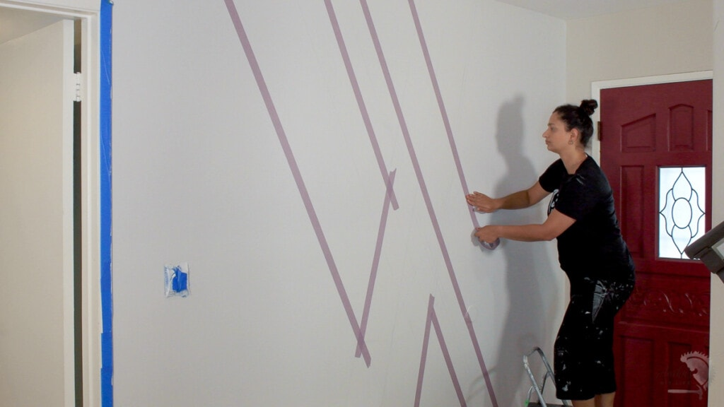Woman applying tape on the wall to make a concrete accent wall