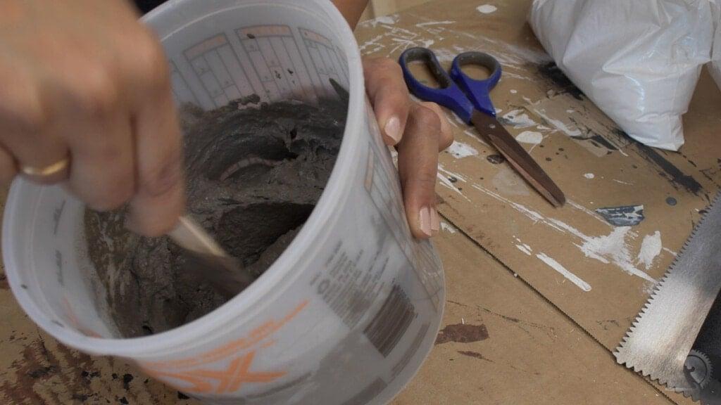 woman mixing concrete for a DIY concrete wall