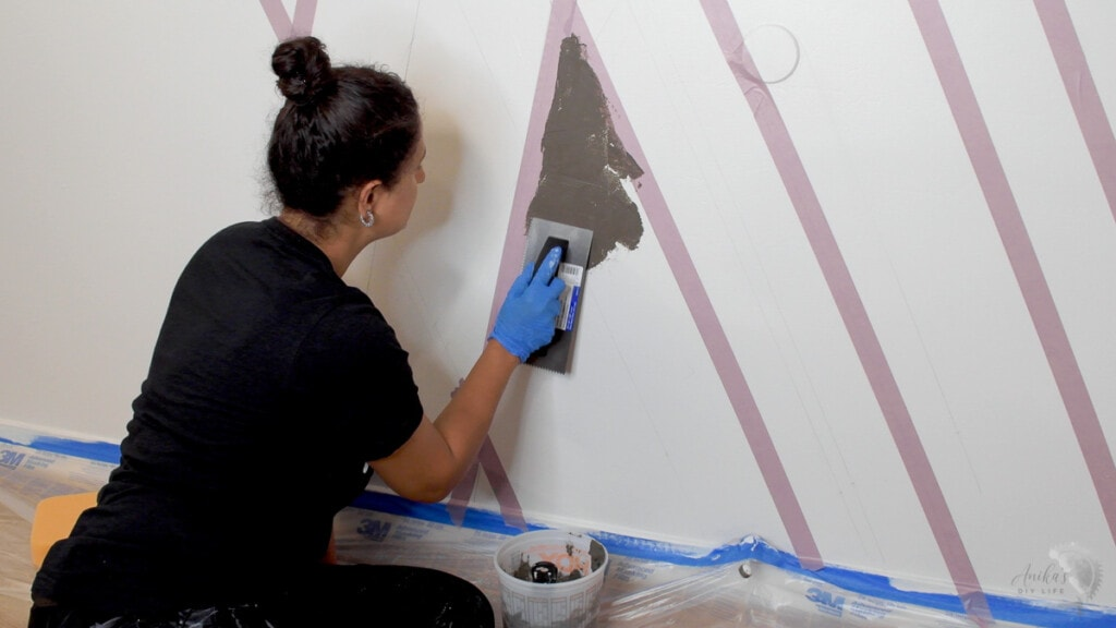 Woman applying cement to the wall