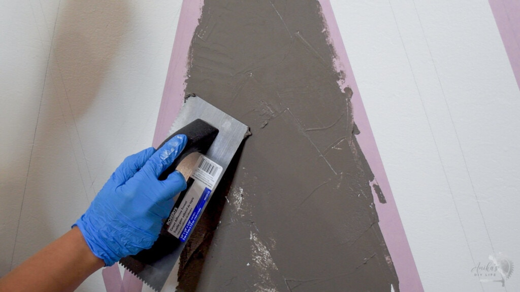 close up of woman applying concrete on the wall.