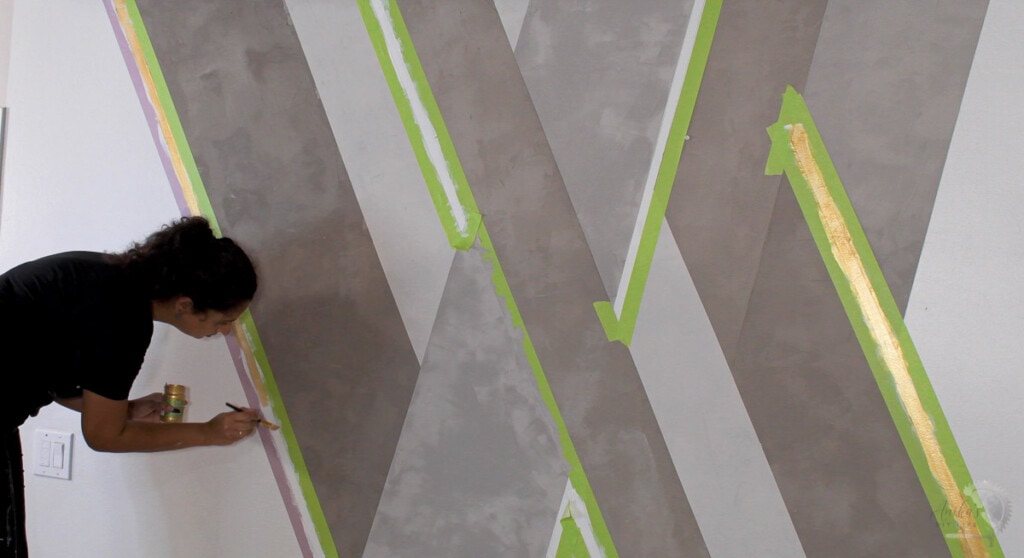 woman painting a gold stripe on a cement accent wall