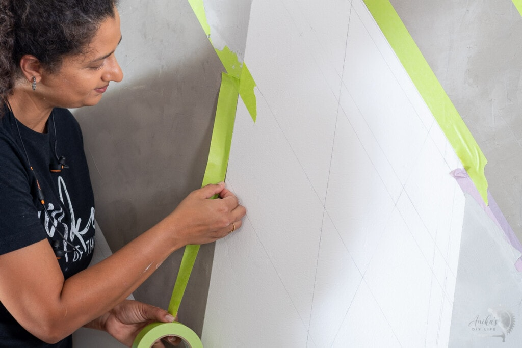 Woman applying tape to the concrete wall for a gorgeous accent wall