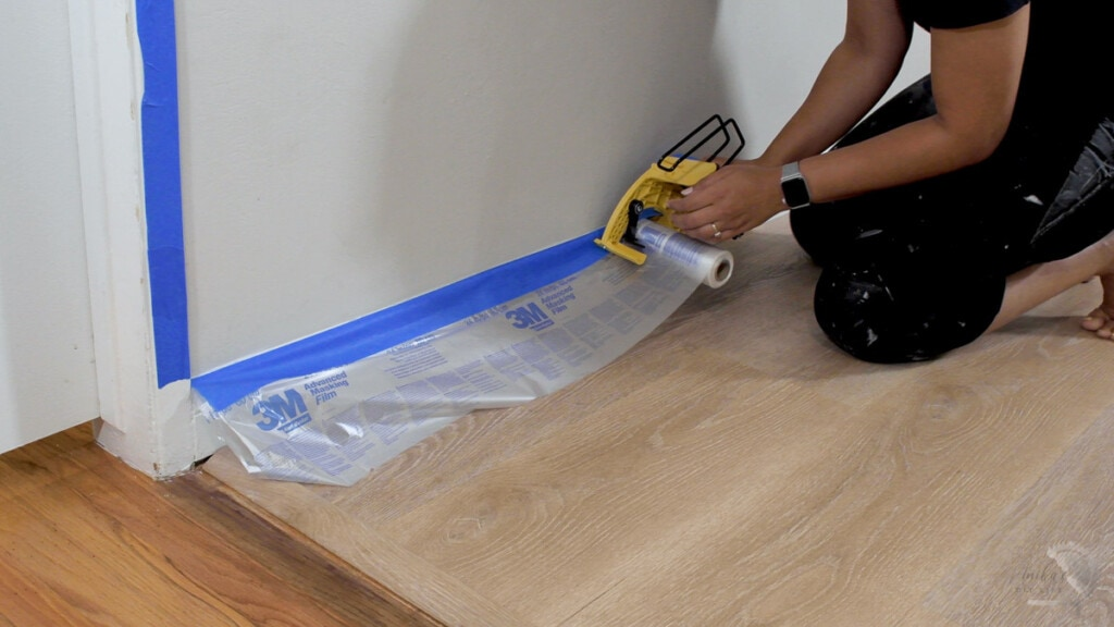 Woman applying tape and masking fil to cover the baseboard and floor before painting
