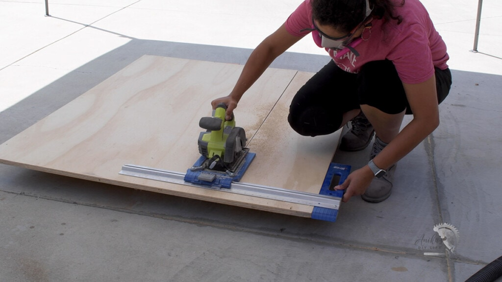 woman ripping plywood using a circular saw and a rip cut guide