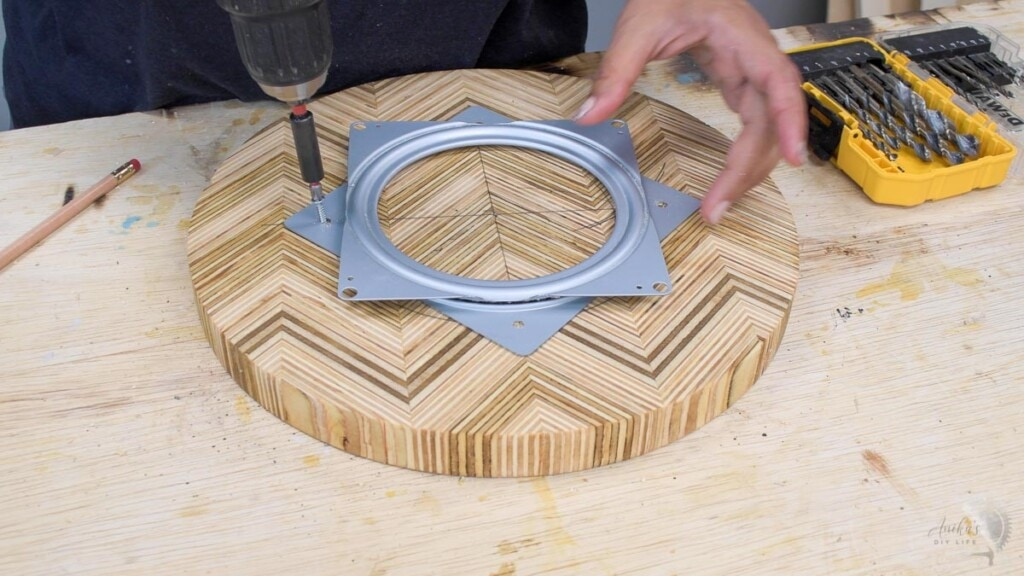 attaching the lazy susan top to the hardware with screws