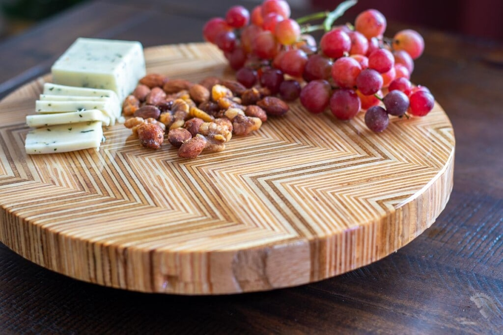 DIY Lazy Susan using Patterned Plywood with cheese , nuts and grapes on dining table