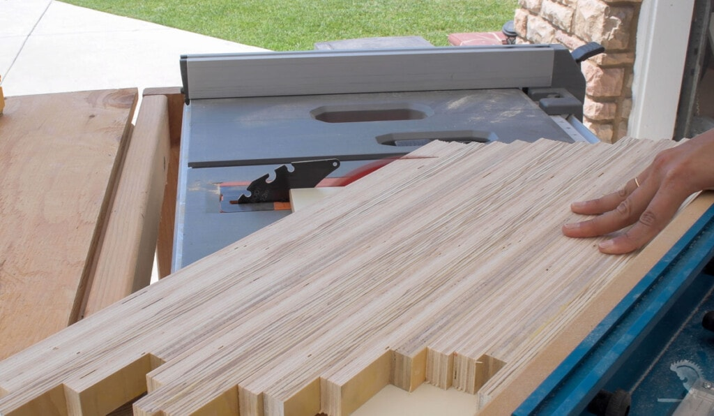 Using a crosscut sled on table saw to cut the patterned plywood panel