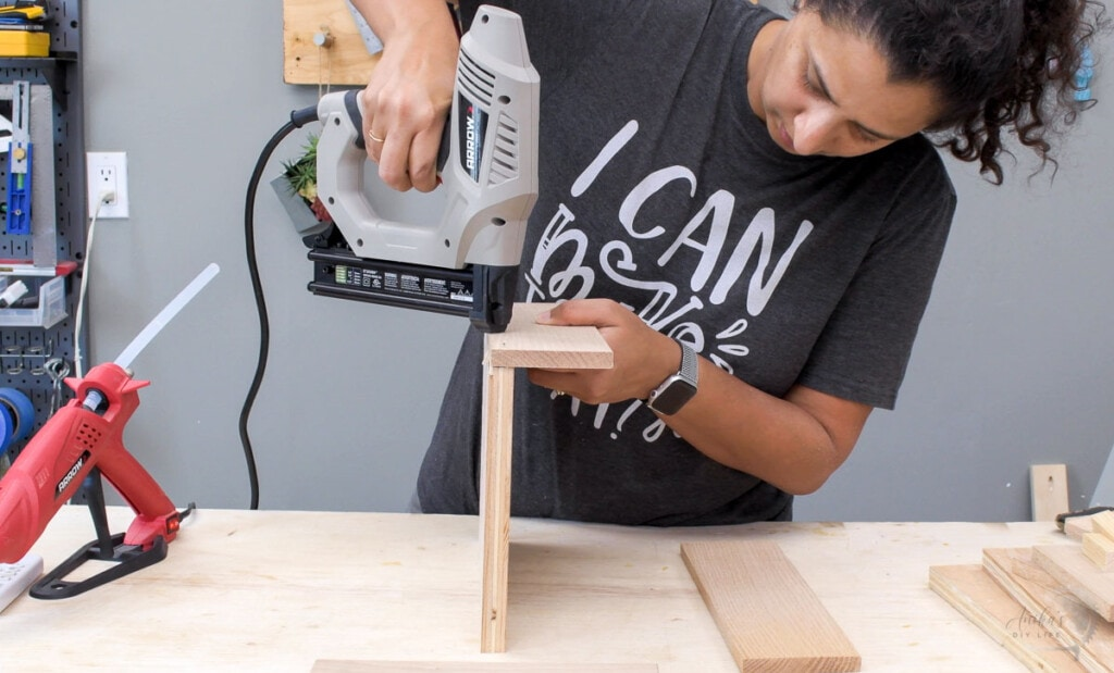 Woman using a nail gun to attach the boards for the multiple device charging station