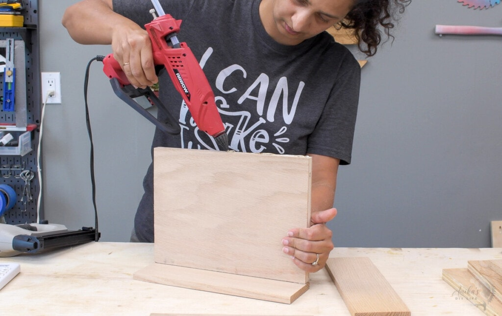 Woman Using hot glue to hold boards in place