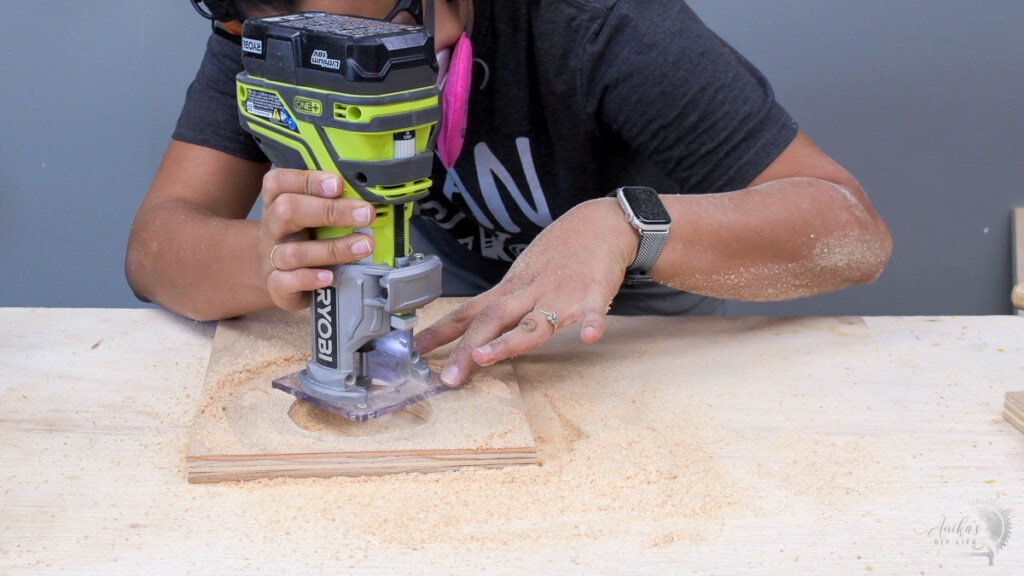 woman routing plywood to accomodate the wireless charger