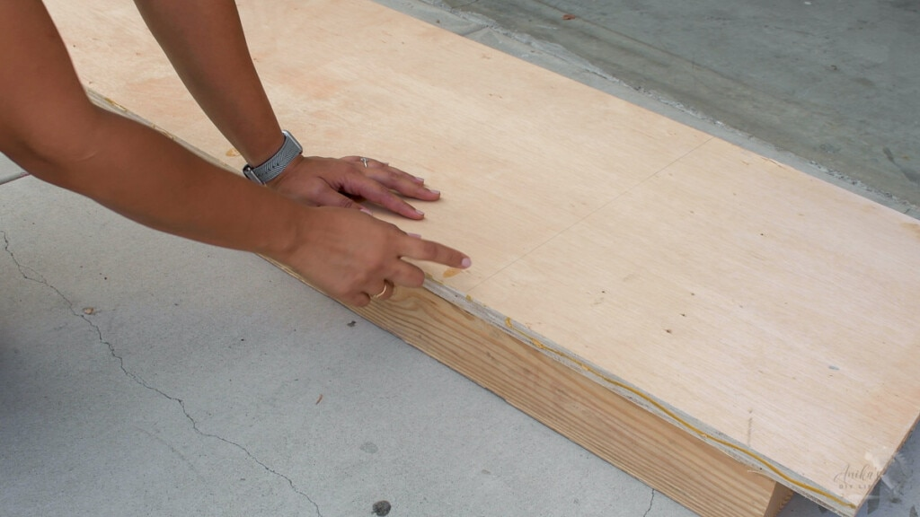 supporting the plywood using boards on floor to cut with a circular saw