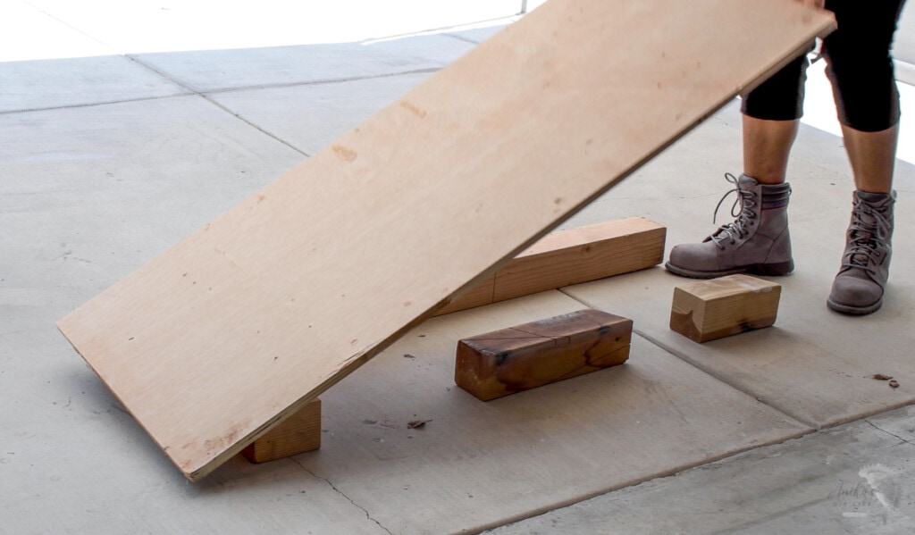 woman setting up the plywood to cut on the floor using structural lumber