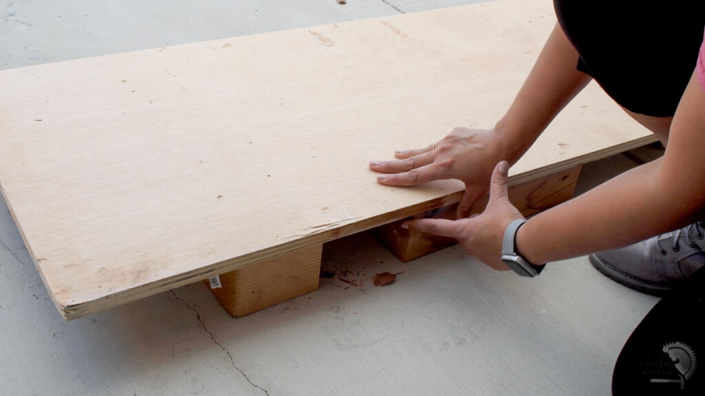 woman setting up plywood to cut on the floor with 4x4 blocks