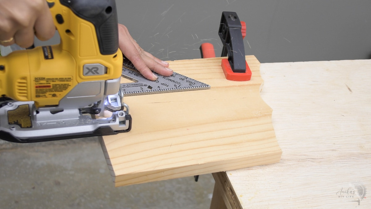 using a speed square to guide a jigsaw to cut a straight line on a board clamped on a workbench